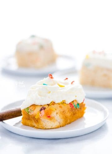 Slice of Gluten Free Fruity Pebbles Cake on a white plate.