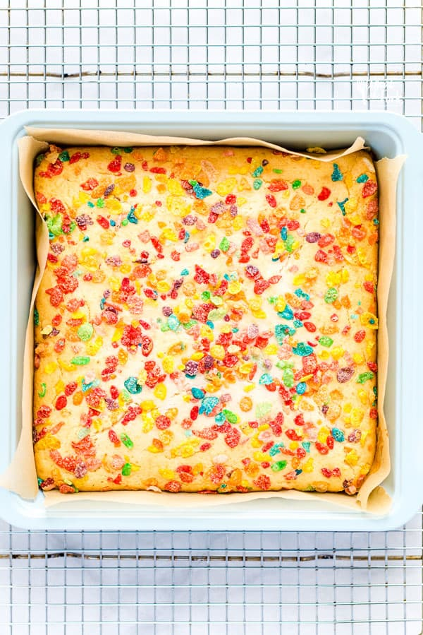 Baked Gluten Free Fruity Pebbles Cake with Cereal Milk in a square baking pan on a wire rack