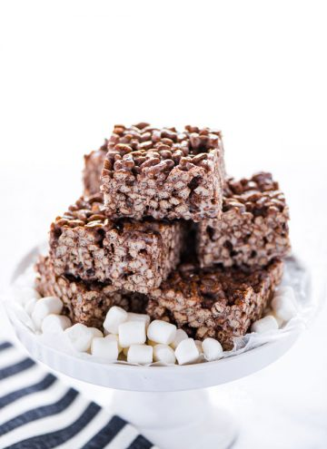 Gluten Free Chocolate Rice Krispie Treats stacked on a white cake stand garnished with mini marshmallows