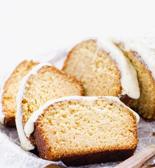 Gluten Free Eggnog Bread with Eggnog Icing sliced on a wood platter lined with wax paper