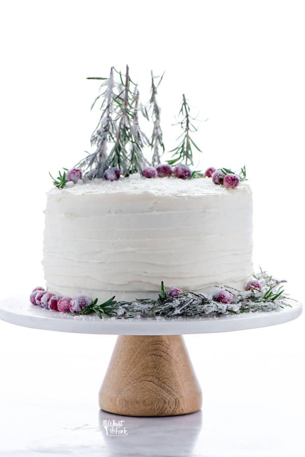 Gluten Free Gingerbread Cake on a cake stand decorated with sugared cranberries and sugared rosemary