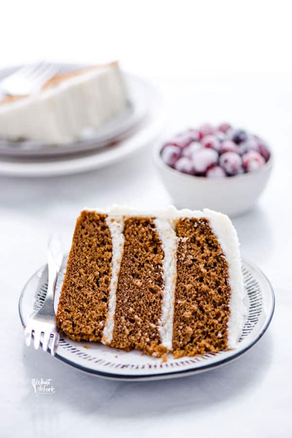 A slice of 3-layer gluten free gingerbread cake on a plate with a fork