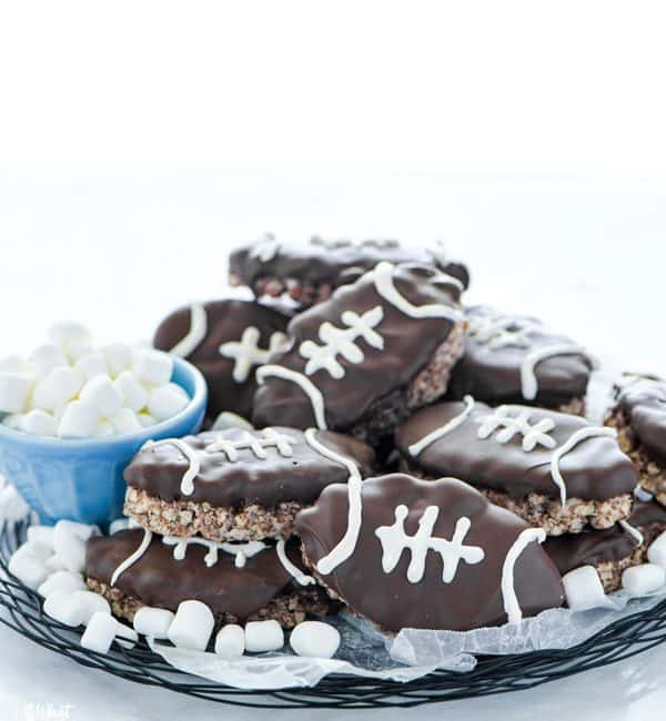 Football Rice Krispie Treats on a wax paper lined wire plate garnished with mini marshmallows