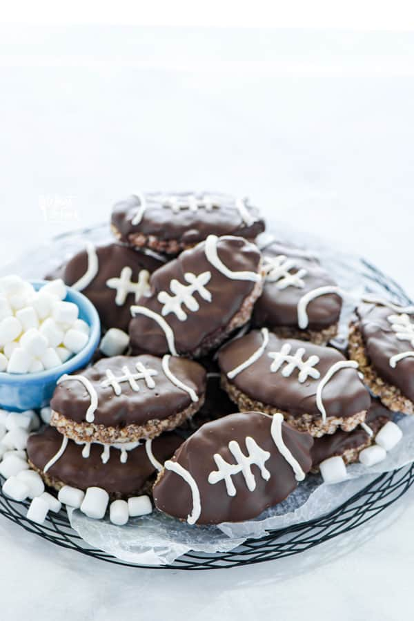 Football Rice Krispie Treats on a black wire platter garnished with mini marshmallows