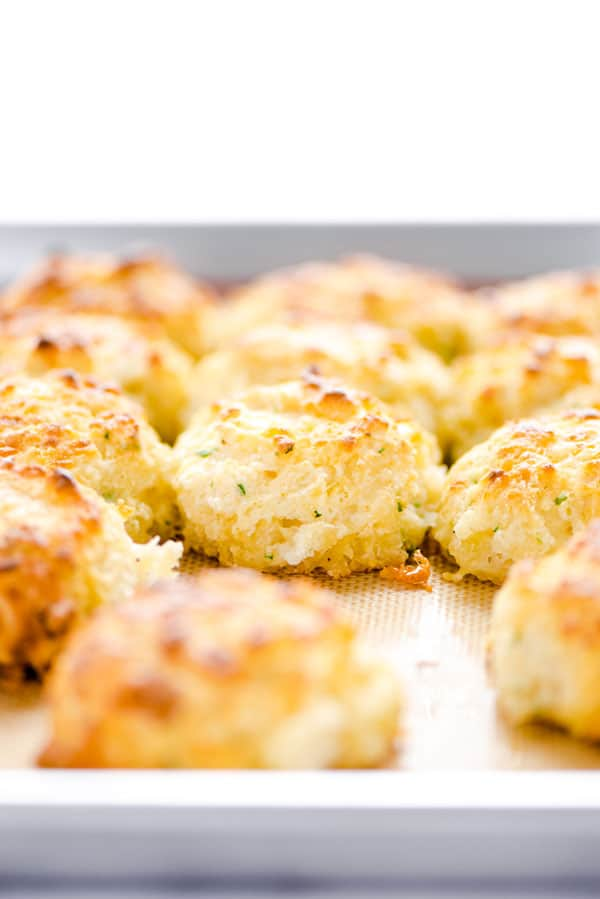 Gluten Free Cheddar Bay Biscuits on a Silpat lined half sheet pan