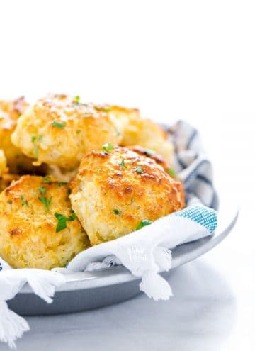 Gluten Free Cheddar Bay Biscuits in a towel lined silver serving bowl