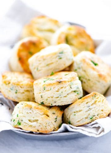 finished gluten free biscuits recipe with garlic and herbs featuring biscuits piled on a bread plate