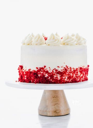 A gluten free Red Velvet Cake on a white marble cake stand with a wood base. The cake is decorated with cream cheese frosting and red velvet cake crumbs.