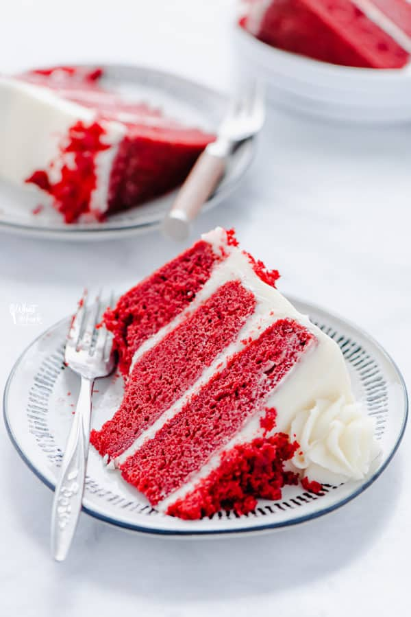 A slice of Gluten Free Red Velvet Cake on a small white plate with a bite taken out