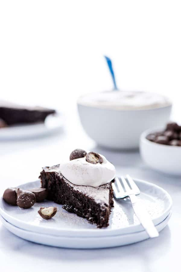 A slice of flourless chocolate peanut butter cake on a white plate garnished with whipped cream and chocolate covered peanuts
