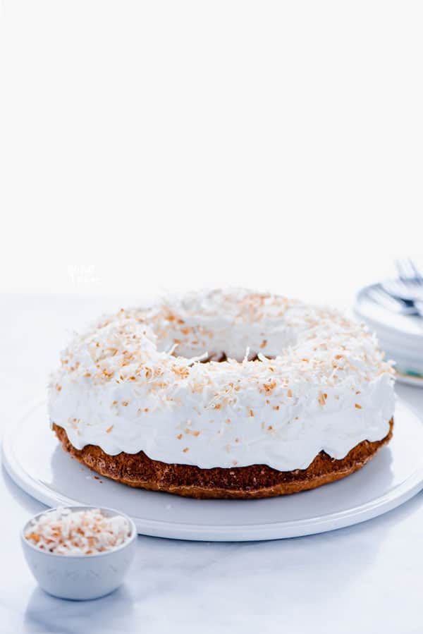 Gluten Free Coconut Pound Cake with Coconut Frosting and Toasted Coconut on a flat white cake plate