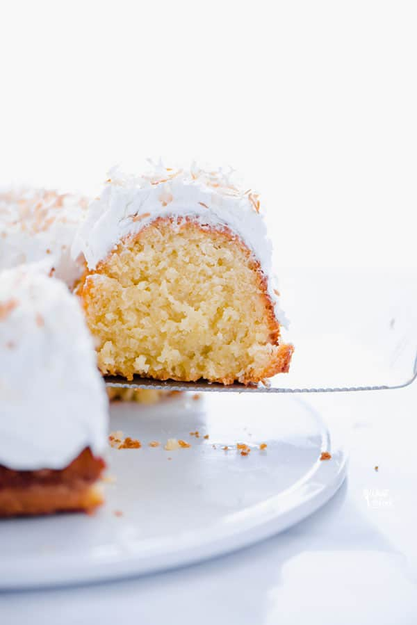 This is a simple, easy recipe for Coconut Pound Cake - aka Coconut Bundt Cake. It's full of coconut flavor from coconut extract and shredded coconut and is topped with the most delicious, creamy coconut icing and garnished with toasted coconut. It's a perfect dessert for a crowd or for holidays, birthday cake, and gatherings. It's moist, dense, and has a tender crumb that's addicting. Gluten Free Cake recipe from @whattheforkblog - visit whattheforkfoodblog.com for more gluten free desserts.