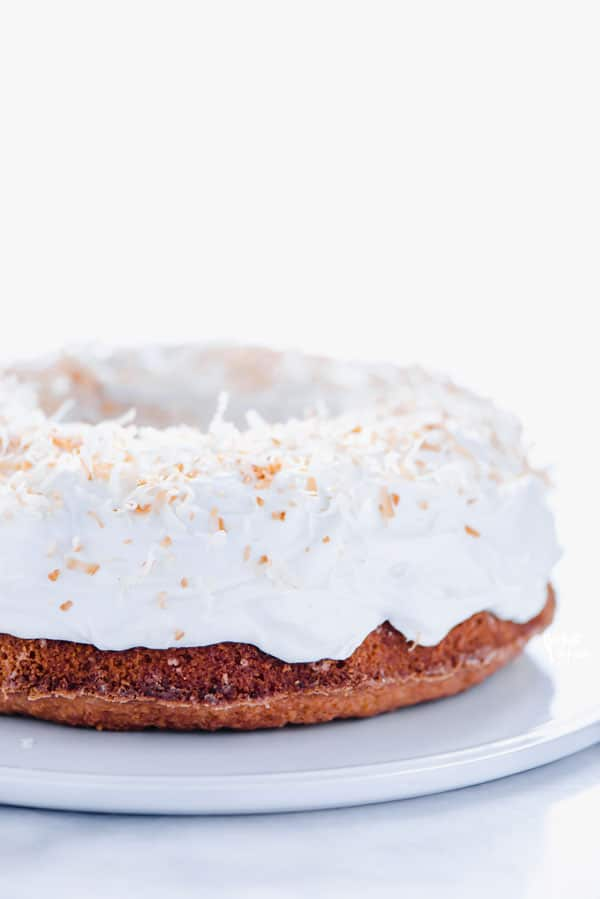 Gluten Free Coconut Pound Cake with Coconut Frosting on a white cake plate