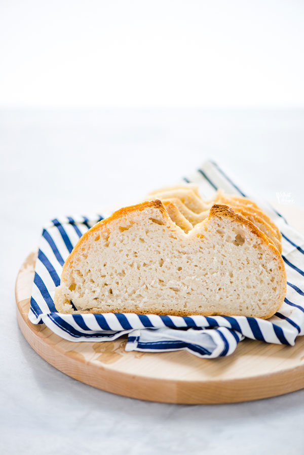 sliced gluten free sourdough bread on top of a white and blue striped napkin on a round wood cutting board