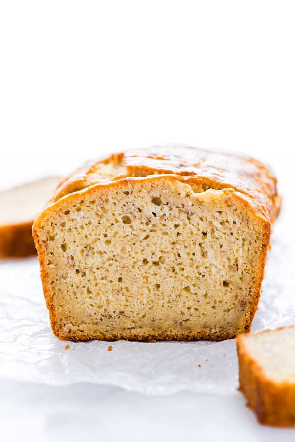 A loaf of Gluten Free Sourdough Banana Bread sliced on a piece of wax paper