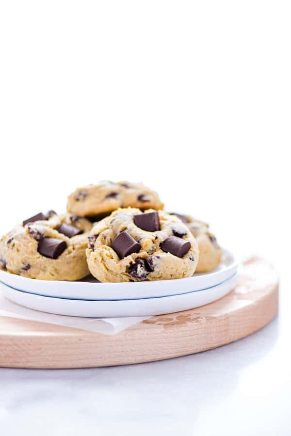 Gluten Free Sourdough Chocolate Chip Cookies on a small stack of white plates on top of a round wood cutting board