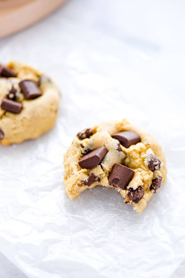 A gluten free sourdough chocolate chip cookie on top of parchment paper with a bite taken out