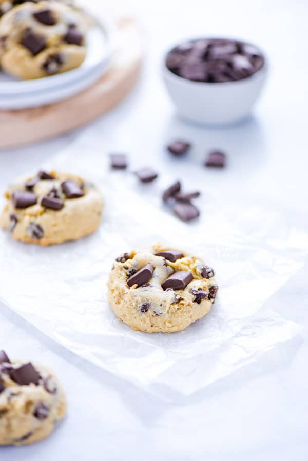 Gluten Free Sourdough Chocolate Chip Cookies on white parchment paper with chocolate chunks and a plate of cookies in the background