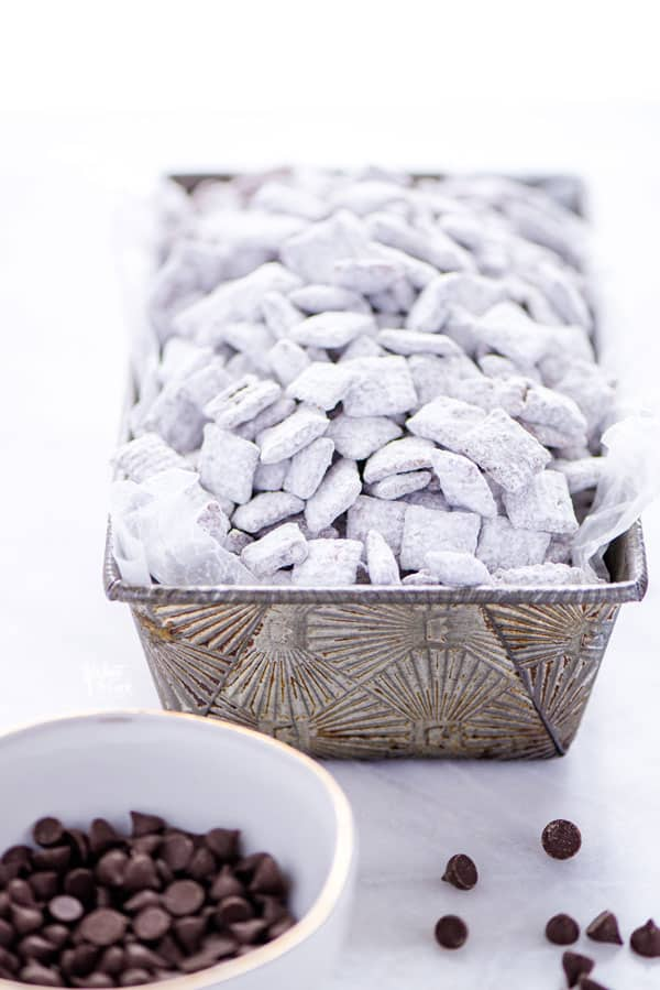 Gluten Free Puppy Chow in a silver loaf pan for serving