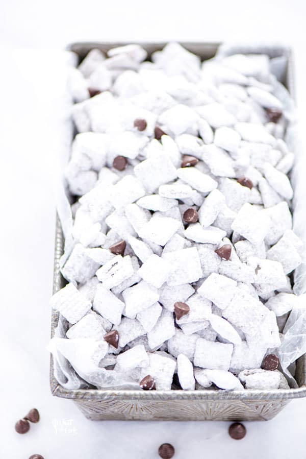 Super simple Gluten Free Puppy Chow - AKA Muddy Buddies is everyone's favorite sweet snack. You only need a few ingredients to make it - Chex cereal, chocolate chips, butter, vanilla, peanut butter, and powdered sugar. You can even make vegan muddy buddies by using vegan butter and dairy free chocolate chips. This no bake recipe takes less than 15 minutes to make too! The recipe calls for semi-sweet chocolate but you can use milk chocolate or dark chocolate if you prefer.