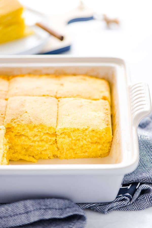 Baked and sliced gluten free sourdough cornbread recipe still in a gray stoneware pan on top of a blue kitchen towel