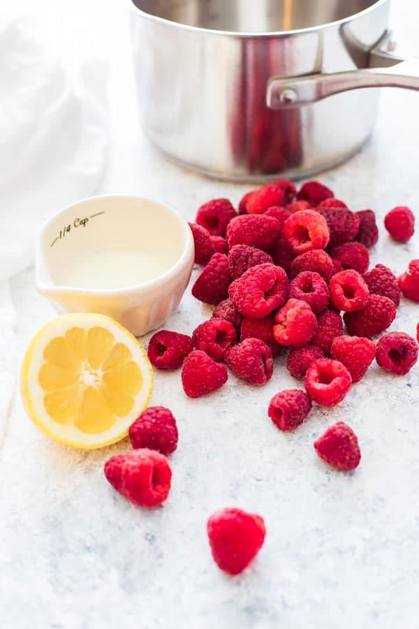 Fresh raspberries and lemon ready to be turned into raspberry sauce