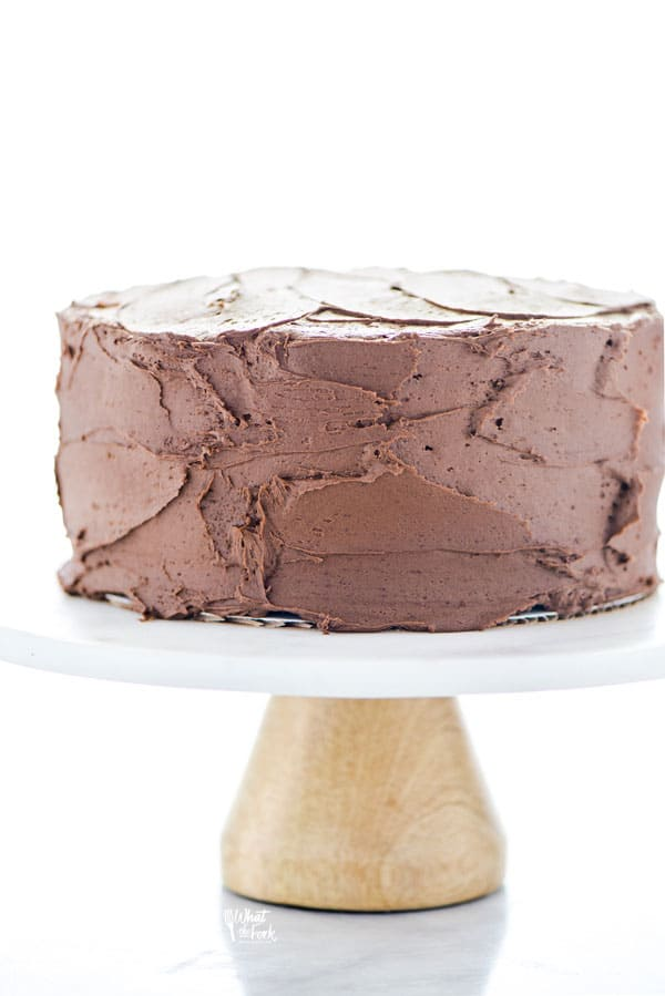 a baked and frosted gluten free sourdough chocolate cake recipe on top of a white cake stand with a light colored wood base
