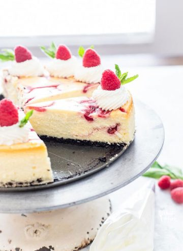 White Chocolate Raspberry Cheesecake on a cake stand with one slice missing, ready to be served