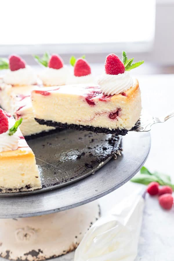 White chocolate raspberry cheesecake being served with one slice being lifted by a pie server