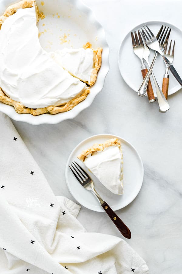 overhead shot of a slice of maple cream pie on a white plate with a wood trimmed fork next to the whole pie and a stack of plates topped with forks
