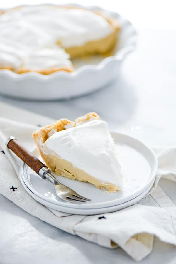 A slice of maple cream pie on a white plate with a wood trimmed fork