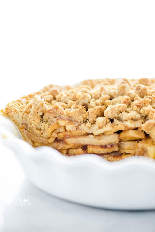 straight on shot of a gluten free apple crisp pie in a white pie dish, that's been cut into and served
