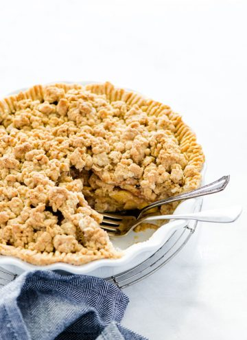 Apple crisp pie in a white pie dish with a piece removed and two forks in the spot of the missing slice of pie