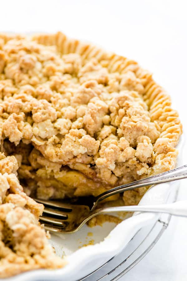 Gluten free apple crisp pie with a piece removed and two forks in it's place