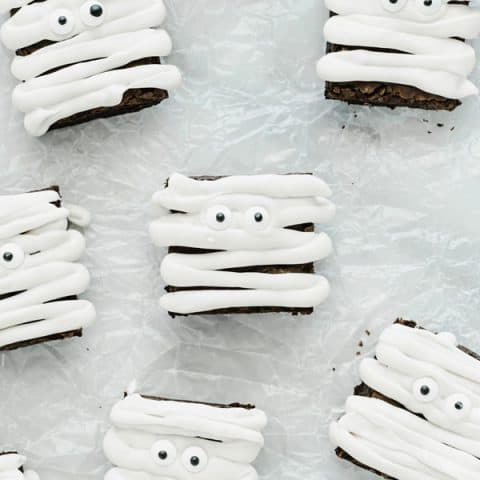 Gluten Free Mummy Brownies decorated for Halloween on crinkled wax paper