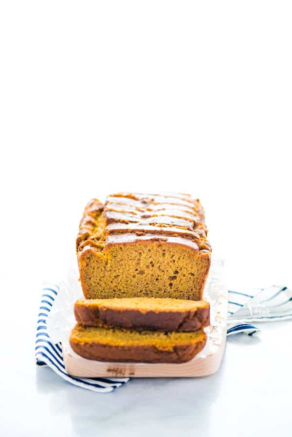 Sliced gluten free pumpkin spice bread on a small wood rectangular cutting board on top of a blue and white striped napkin