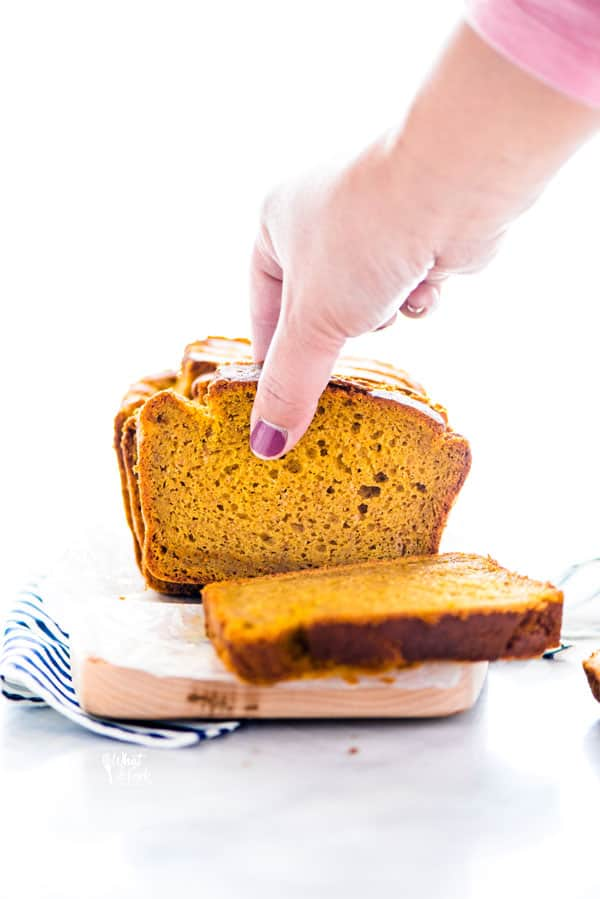 a hand grabbing a piece of gluten free pumpkin spice bread from above
