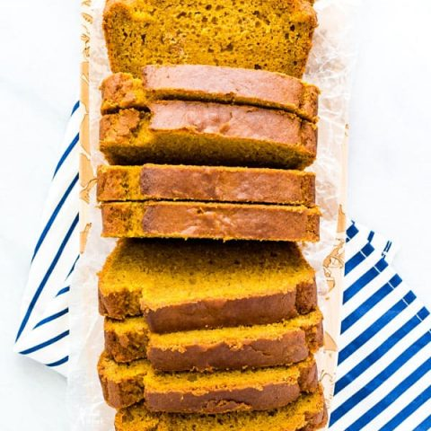 overhead shot of slice gluten free pumpkin spice bread on a narrow wood rectangular cutting board