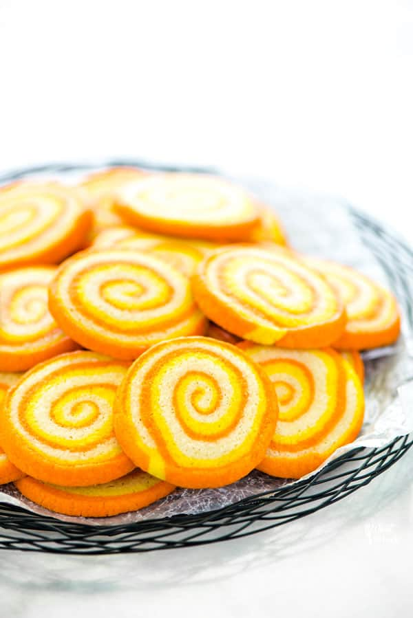 Gluten Free Candy Corn Pinwheel Cookies on a black wire platter lined with wax paper