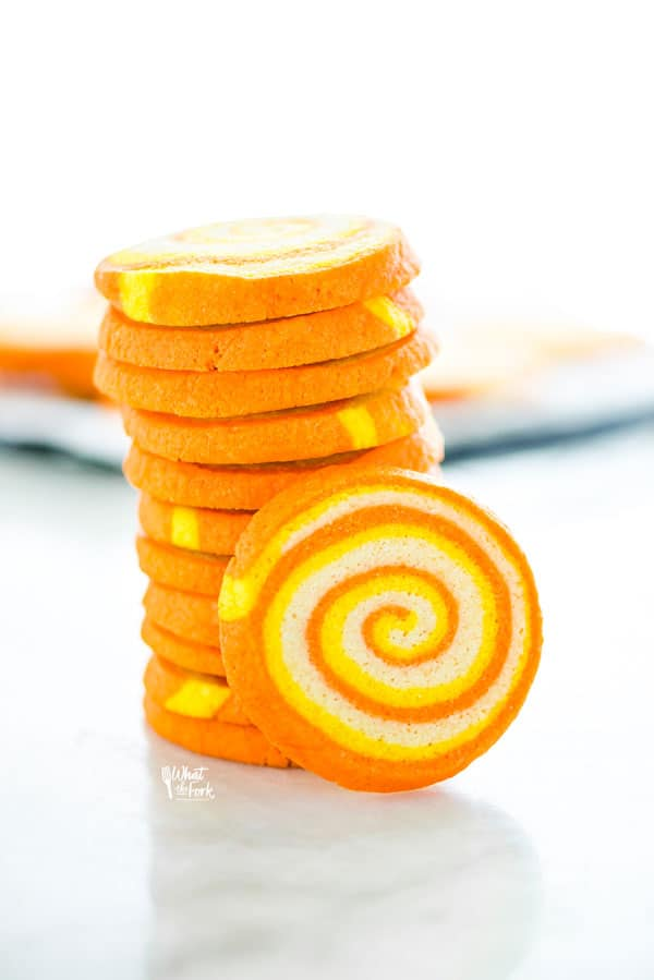 a stack of gluten free candy corn pinwheel cookies on a marble surface