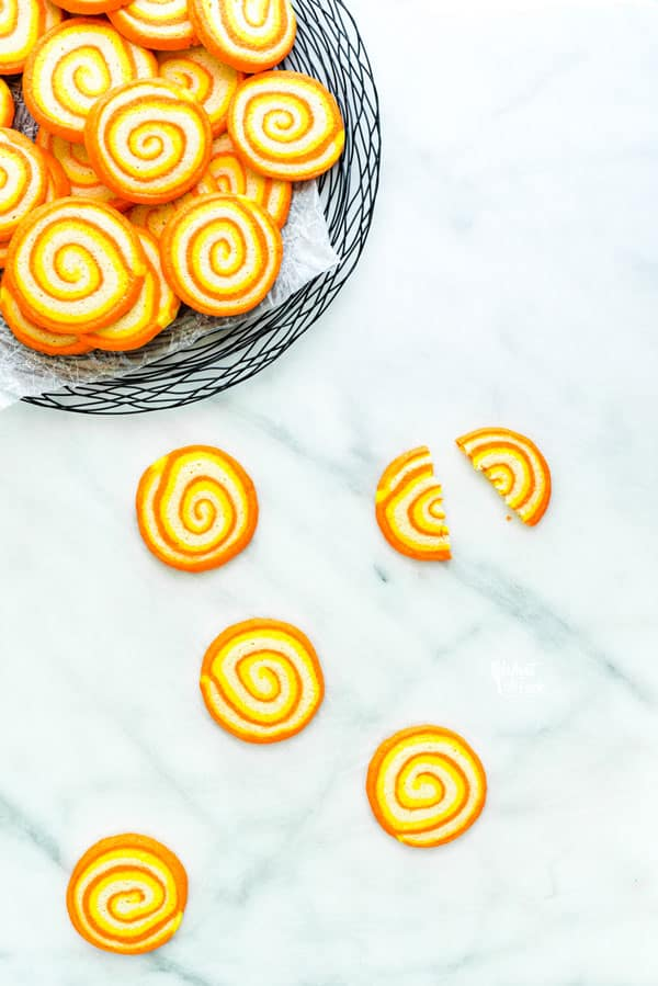 overhead shot of gluten free candy corn pinwheel cookies on a white marble surface
