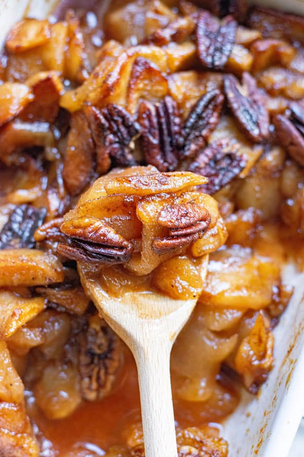 cinnamon baked apple slices being dished out of a white casserole dish with a wooden spoon