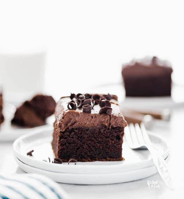 a slice of gluten free chocolate pumpkin cake on a stack of round white plates with a glass of milk and more slices of cake in the background