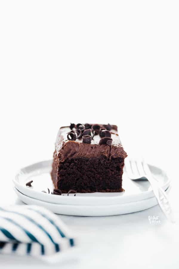 a slice of gluten free chocolate pumpkin cake on a stack of white plates