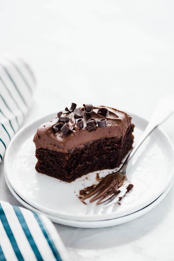 a slice of gluten free chocolate pumpkin cake on a white plate with a forkful of cake eaten