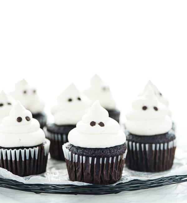 gluten free Halloween ghost cupcakes on a black wire platter lined with wax paper