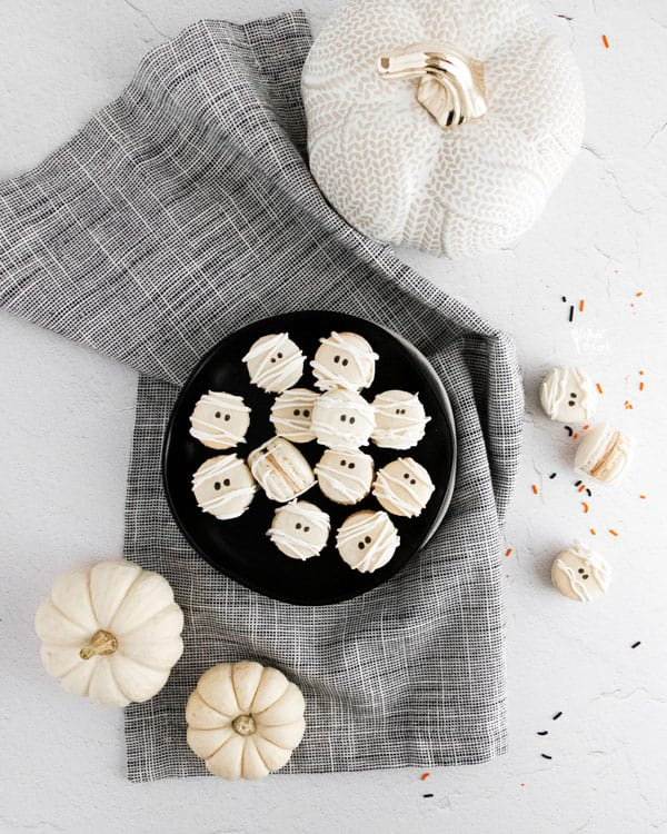 Mummy Macarons with Maple Cinnamon Filling on a black plate on top of a black and white cloth napkin surrounded by white pumpkins