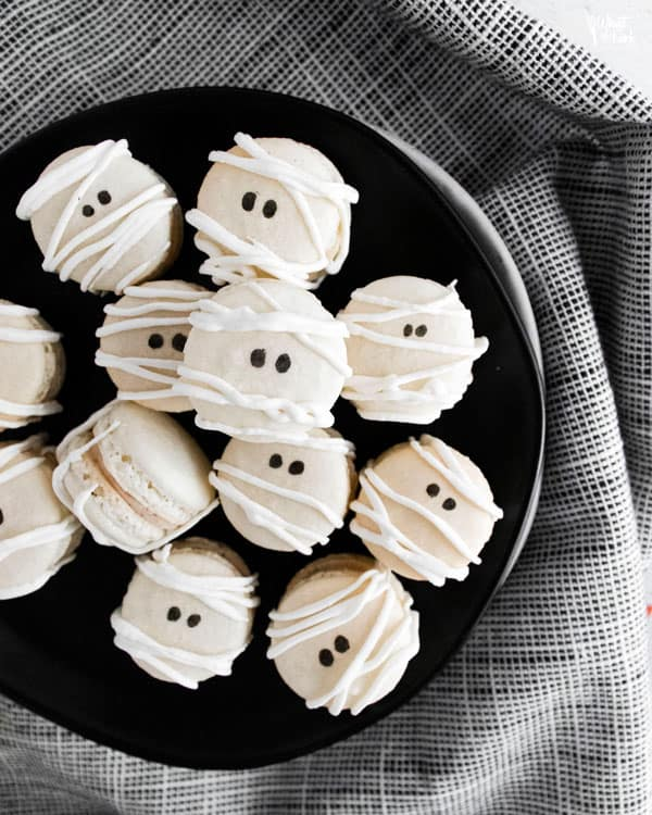 Mummy Macarons with Maple Cinnamon Filling on a black plate over a black and white napkin