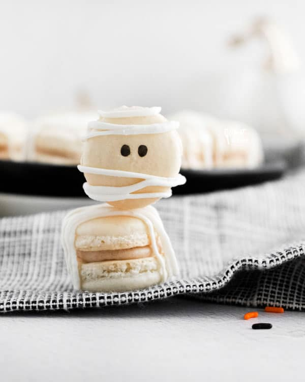 2 Mummy Macarons with Maple Cinnamon Filling stacked on top of each other on a black and white cloth napkin
