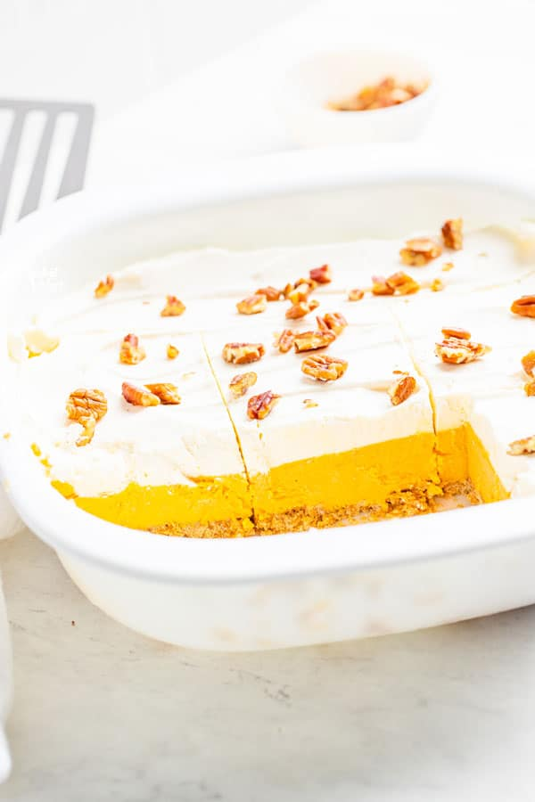 Gluten free pumpkin lush cake in a white pan that's been cut into